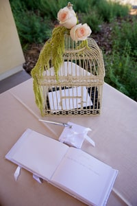 Guest register table has birdcage décor with peach rose accent