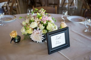 Closeup of basic wedding dinner centerpiece for a round table and table number sign