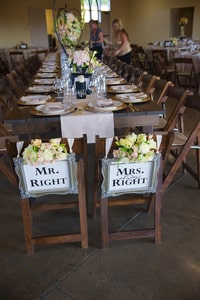Mr. and Mrs. Right chairs at wedding dinner long table where newly-married couple can enjoy their guests and the occasion