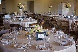 Overview of wedding dinner round tables, place settings, and centerpieces