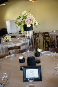 Closeup of cylindrical wedding dinner centerpiece vase for a round table and table number sign