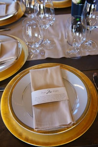 Closeup of wedding dinner place setting showing gold charger and gold-edged china