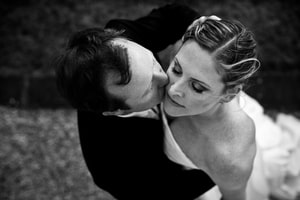 Black-and-white photo of bride and groom caress