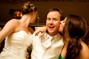 Groom getting a kiss from a bridesmaid