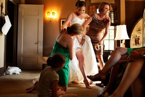 Bride getting dressed with help of mother and bridesmaids