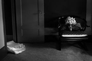 Black and white photo of bridal bouquet and disappearing bridal gown