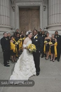 Formal photo of bride, groom, and wedding party in front of Sacramento Grand Ballroom, Sacramento, CA
