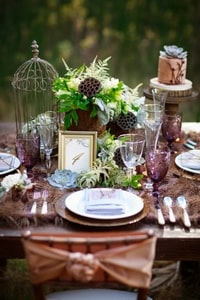 Forest floral arrangement accented with birdcage forms an appropriate centerpiece for a forest wedding