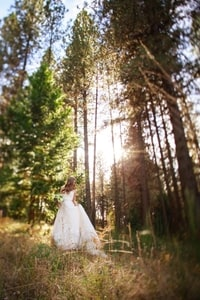 Bride walking through a meadow in sunlight streaming through the trees