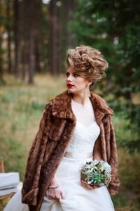 Bride with bouquet, fur coat, makeup, hair and jewelry with the forest as a backdrop