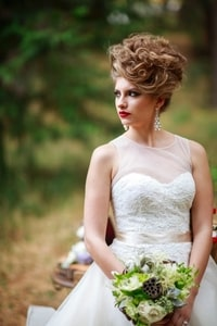 Closeup of bridal gown and forest-based floral bouquet