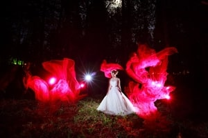 For dramatic effect, fire is simulated in this evening forest photo of a bride in a meadow