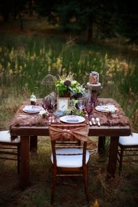The wooden table and wooden chairs fit right in for a forest wedding