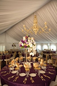 Purple tablecloths, gold accents, and floral arrangements that seem to float in a tent with flowing satiny ceiling for the wedding dinner; Grand Island Mansion, Walnut Grove, CA