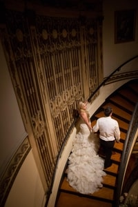 Bride and groom walking up stairs showing bridal grown train; Grand Island Mansion, Walnut Grove, CA
