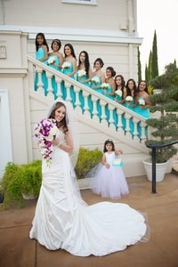 Bride with bridal bouquet in gown with train, flower girl, and bridesmaids in blue on the stairs; Grand Island Mansion, Walnut Grove, CA