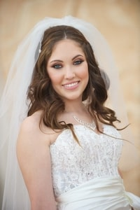 Bride with veil, hair, makeup, jewelry, and lace bodice of wedding gown