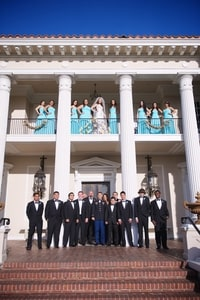 Bride and bridesmaids on the balcony with groom and groomsmen on the patio below; Grand Island Mansion, Walnut Grove, CA