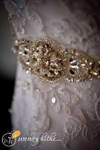 Closeup of wedding gown details showing lace and brooch