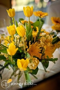 Stunning flower arrangement of yellow and gold for wedding table