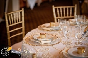 Gold accents on wedding place setting including guest gift