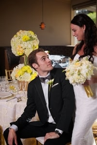 Yellow rose bridal bouquet, boutineer, and floral centerpiece for wedding dinner