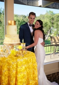 Yellow tablecloth under 4-tier yellow and gold wedding cake