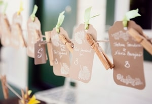 Wedding reception name tags showing name and table number; held to twine clothesline with clothespins
