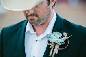 Groom's boutonierre shows rustic detail like weathered wood, metal, and twine