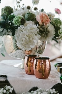 Hammered copper mugs provide western accent for wedding reception table
