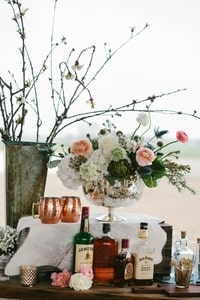 Bar at wedding reception: rustic flower arrangements