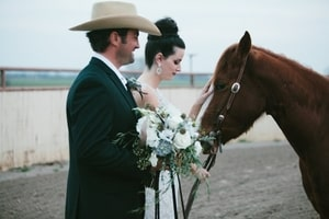 Bride and groom in profile with horse