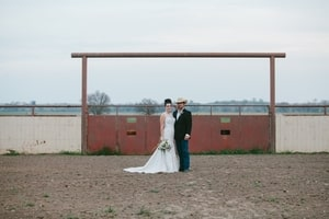 Bride and groom in front of rusted metal gate in the horse arena at Murieta Inn and Spa, Rancho Murieta, CA