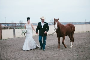 Bride and groom with trotting horse in arena at Murieta Inn and Spa, Rancho Murieta, CA